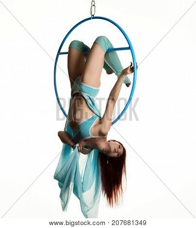 young redhead woman performs acrobatic elements in the air ring.