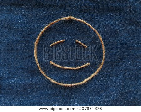 Funny face of twine on denim background.