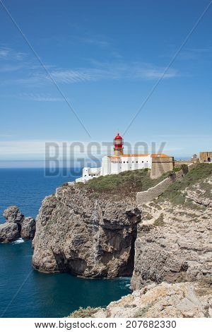 Cabo de Sao Vincente Cape Saint Vicent lighthouse on the rocks above the Atlantic ocean. The most south-western point of Europe. Sagres Algarve region Portugal. Sunny panoramic picture with clear blue sky