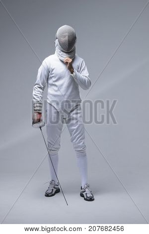 Portrait of a fencer in a fencing mask with a sword on grey background