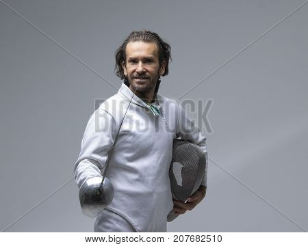 Portrait of cheerful  fencer holding his fencing mask in the hand with the sword on grey background