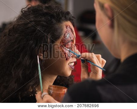 Make-up artist make the girl halloween make up in studio.Halloween face art.Woman applies on professional greasepaint on the face of spanish girl.War-paint with blood, scars and wounds.