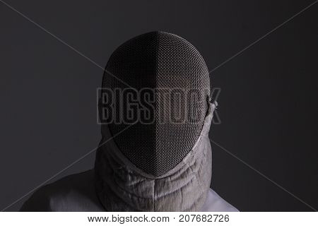 Portrait of a fencer in fencing mask on grey background
