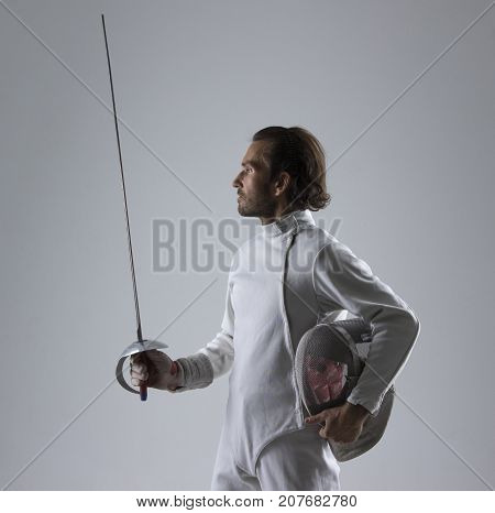 Portrait of the  fencer holding his fencing mask in the hand with the sword on grey background