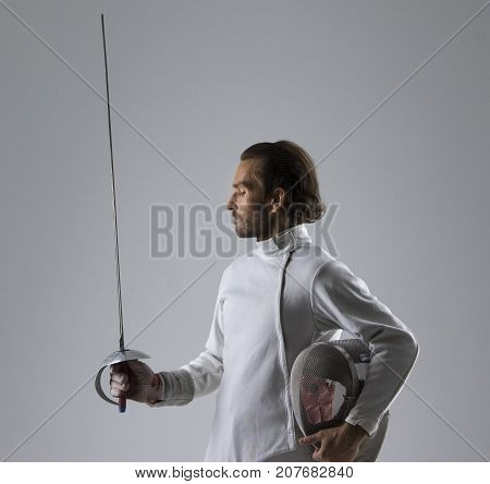 Portrait of concentrated  fencer holding his fencing mask in the hand with the sword on grey background
