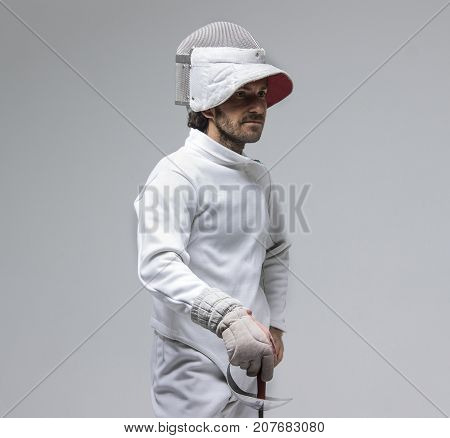 Portrait of a concentrated  fencer  with a sword on grey background