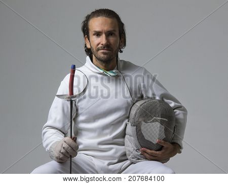 Professional male fencer holding mask and sabre while sitting on chair. Studio shot