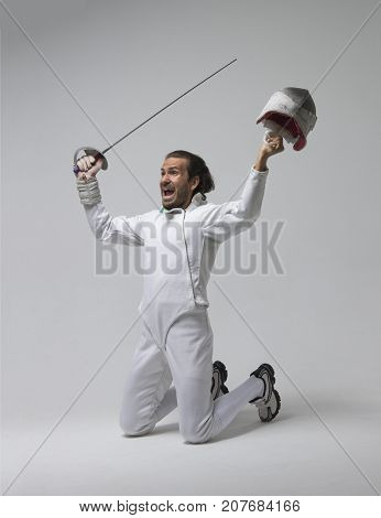 Portrait of a  fencer  with a sword holding his mask in all the glory.Celebrating the victory.Studio shot