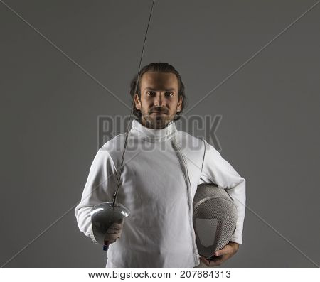 Portrait of   fencer  with the sword  while holding his mask in the hand.Studio shot