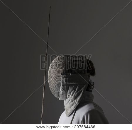 Profile of a fencer in fencing mask with the sword on grey background