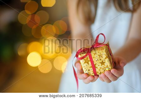 Child Gently Holds In The Hand A Christmas Gift