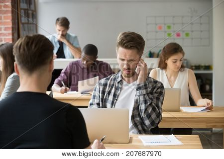Perplexed casual entrepreneur making phone call at work in shared office space. Concerned project manager having unpleasant conversation with clients or business partners, being on hold for too long.