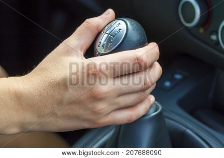 Female driver hand shifting gear manually. Girl driving a car
