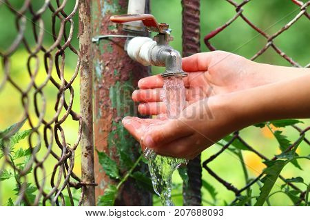 Close up child hands with water drops from old grunge brass faucet on green bokeh background. Water shortage and earth day concept.