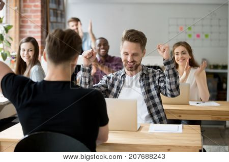 Young casually dressed male office worker throws hands in air celebrating achievement at work. Coworkers around cheer and clap hands. Rewarding outcome, received promotion, achieved success concept.