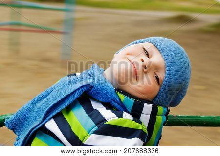 the image boy in a cap and scarf riding on a carousel