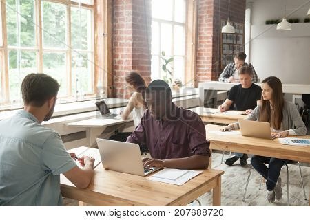 Multiethnic group of casual coworkers at work in shared loft office. Corporate team working on laptops, taking notes in shared room, brainstorming about new project, teamwork and collaboration concept