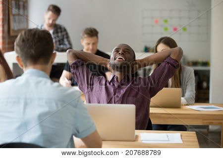 Relieved african american entrepreneur relaxing with hands behind head, happily resting after finished work. Office worker done with task before his coworkers, colleagues are busy in shared office.
