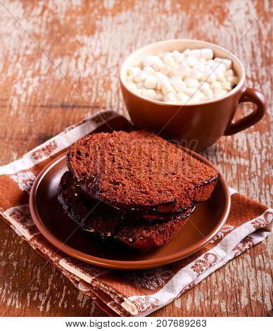 Chocolate cake with chocolate icing and drink with marshmallow