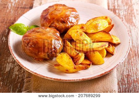 Beefsteaks wrapped in bacon and roast potato on plate