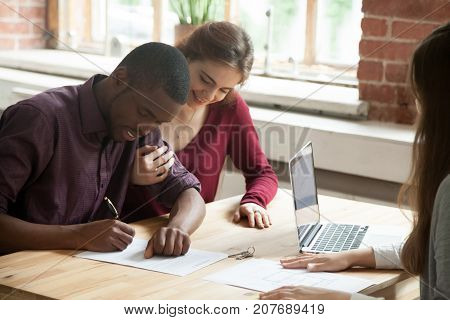 African american man signing home purchase agreement in front of realtor, his smiling wife watching contract being signed. Young multiethnic family leasing new apartment. First time buyers concept.