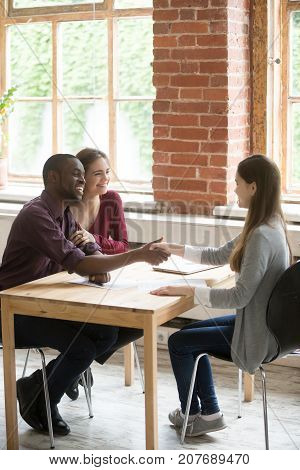 Happy smiling african american man shaking hands with real estate agent. Husband and wife signed rental lease agreement. Young multiethnic couple got great deal, rented or purchased new home concept.