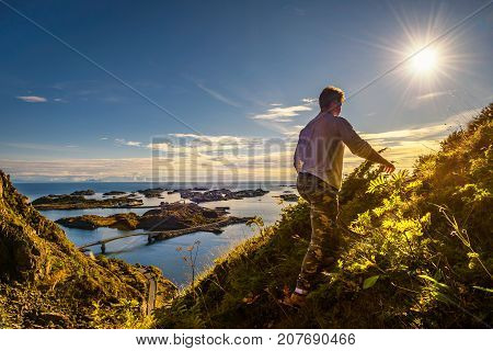 Male hiker going to the top of mount Festvagtinden with views over the village of Henningsvaer on Lofoten islands in Norway