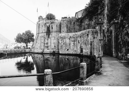 Kotor, Montenegro. Entrance to the Old Town of Kotor, Montenegro during the day. Popular landmark with reflection in the water. Black and white