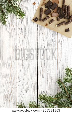Christmas Card with chocolate candies and fir branches on white wooden background. Copy space composition. Top view flat lay overhead