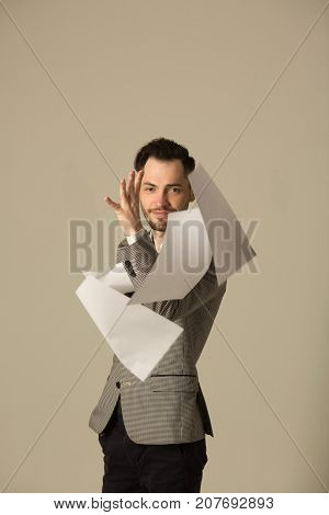a young man in a suit with an unshaven face weary at work with documents, he frees himself without restraining his nerves