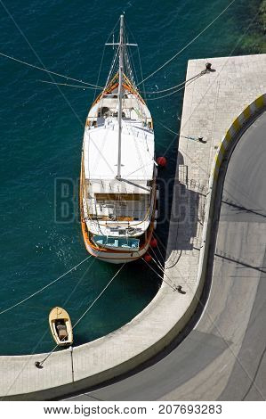 Old wooden sailing boat with lifeboat moored in Omis harbor in Croatia