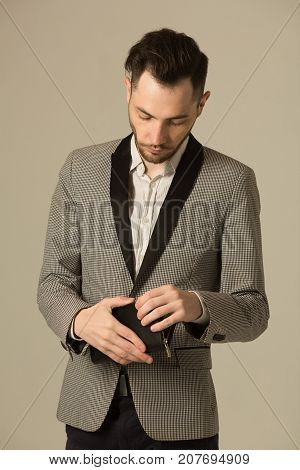 a young man in a suit with an unshaven face in frustration with the lack of money in his wallet