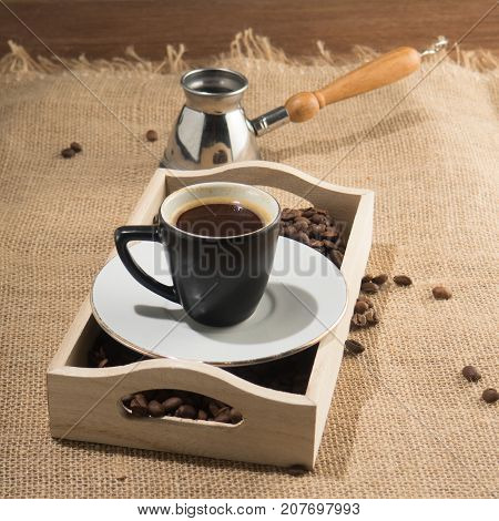 Coffee grains and cup of coffee in wooden box. Strong coffee. Coffee gezve and box on the sackcloth background. Square image