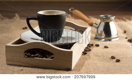 Coffee grains and cup of coffee in wooden box. Strong coffee. Coffee gezve and box on the sackcloth background. Brown image