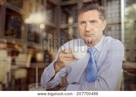 Attractive mid adult man drinking coffee in cafe.