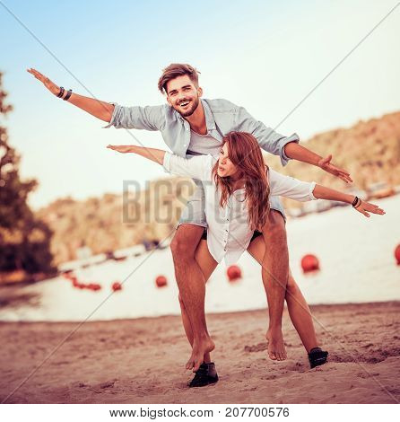 Picture of a joyful couple doing piggyback on the beach.Crazy in love.