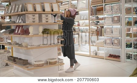 MINSK, BELARUS - OCTOBER 10, 2017. Inside Zara Home retail store in Minsk. A young hipster woman chooses home acessories the store. Shopping