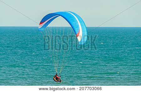Man Paragliding With Blue Parachute Above Water Sea, Clear Sky