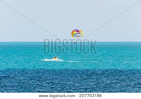 Colored Parasail Wing Pulled By A Boat In The Sea Water, Parasailing Also Known As Parascending Or P