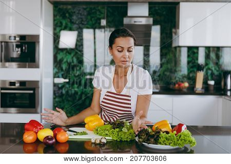 A Young Confused And Thoughtful Woman In Apron Decides What To Cook In The Kitchen. Healthy Food - V