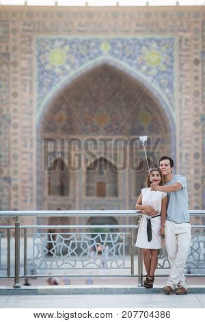 Samarkand Uzbekistan - June 5 2017: A couple takes a selfie in front of the Registan palace Samarkand Uzbekistan.