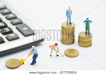 Worker removing coins with background of Businessman standing on coins stacks business concept and Isolated on white background Miniature people removing coins and standing on coins stacks.