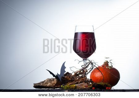 A Glass Of Wine With Decorations For Halloween On The Table