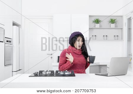Picture of young woman holding a cup hot coffee while looking at the laptop with shocked expression. Shot in the kitchen