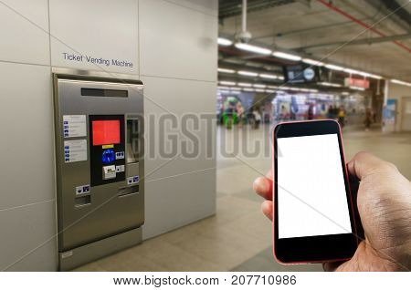 hand holding white blank screen mobile phone with self service ticket or ticket vending machine at train station transportation technology internet network connection and social media concept