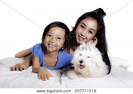 Little girl and her mother lying on the bed with their cute dog isolated on white background