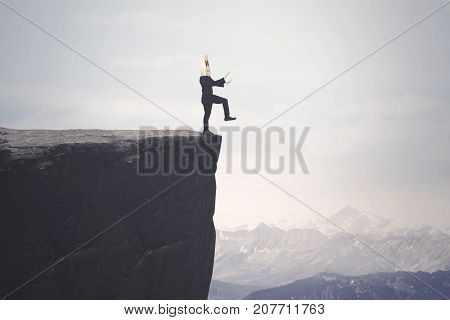 Photo of a disoriented businessman with cardboard head finding a way and walks on the cliff