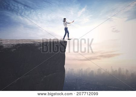 Young businesswoman walking blindfolded on the cliff with a city on the background