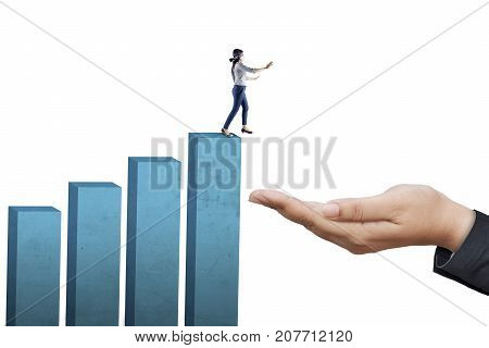 Young businesswoman walking blindfolded on the top of graph while finding a way towards a helping hand