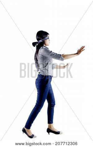 Portrait of young businesswoman blindfolded with a tie while walking in the studio isolated on white background